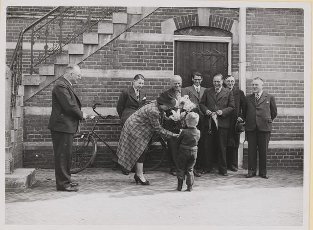 075533 - Gemeente secretaris C.M.H. de Valk vierde op 1 april 1935 zijn 12 1/2-jarig jubileum. foto:  mevr. de Valk krijgt bloemen aangeboden.