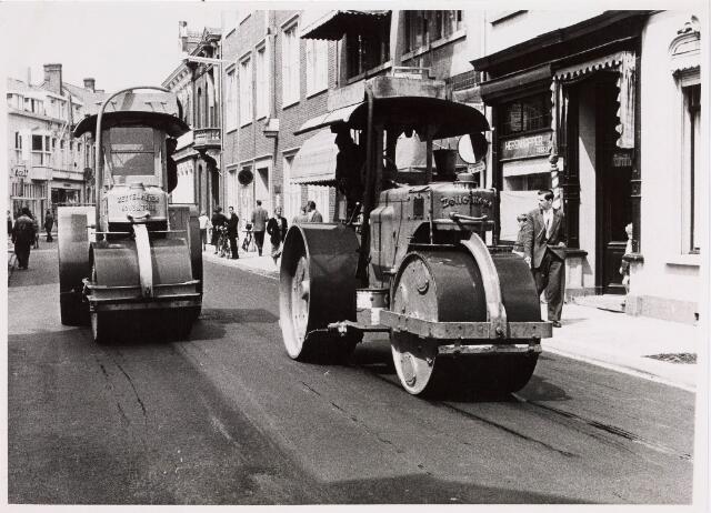 035285 - Walsen in de Willem II-straat voor de nieuwe asfaltering dat klaar kwam op 28 juni 1957; hier bevinden zich de panden nummer 82 en 70, waarbij in de gevel een koninklijk wapen is aangebracht uitgereikt door koningin Emma in 1895 aan kapsalon van de firma Lejeune.