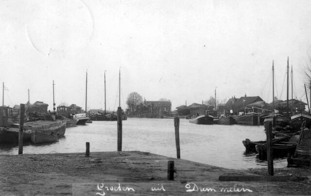 """064886 - De haven van Drimmelen. Zeilschepen met mast en motorboten.  Het riet op schelven rechts boven op de foto behoorde toe aan Stijnis en Vos, dit riet kwam uit de Biesbosch en in die tijd werd riet nog voor allerlei toepassingen gebruikt.    v.l.n.r.  ms """"Geertuida"""", van Huib Brouwers. Deze was ook kolenboer in Drimmelen.  Daarnaast de sloep van A.B. van Loon.  Daarachter tegen de wal(kant) het m.s. """"Vesta"""" van Leen Schuller.  Het schip met de witte roef(woning) is het m.s. """"Vertrouwen"""" van Jaap van de Sluys.  Daarachter het eerste schip tegen de wal onbekend, daarnaast de aak """"Koophandel"""" van Wijnand van Gils uit de Stationstraat te Made.(Dit was toen nog een zeilschip, later is hierin een motor gekomen van 12pk van het merk ABC)     In de midden op de achtergrond het huis/café van Wim Vos    Nu aan de rechter zijde van de foto:   Met witte kop: een klipper, waarschijnlijk van de fam. Stoop uit Made. Daarnaast een onbekende tjalk..  Tweede rij van links naar rechts: onbekende tjalk, m.s."""" Catharina"""" van Janus van der Zanden.  Daarnaast een onbekende luxe motor, geheel aan de binnenkant de luxe motor """"Energie"""" van Willem Norbart uit Made.  De daken rechts zijn van de huizen van Cor Steijnis. Het riet was ook van Steijnis.  De scheepjes (RIETAKEN) op de voorgrond waren van caféhouder Bart de Wijs. Deze werden verhuurd aan de Biesbosch werkers. Hier kon men ook teer en verf kopen voor onderhoud van de schepen."""
