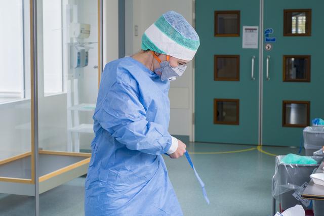 17280294 - Covid-19. Corona. Ziekten. Epidemieën. Pandemie. In de omkleedruimte voor de intensive care van het ETZ (Elisabeth-TweeSteden Ziekenhuis). Een medewerker met extra beschermende kleding zoals de bril en speciaal mondkapje.