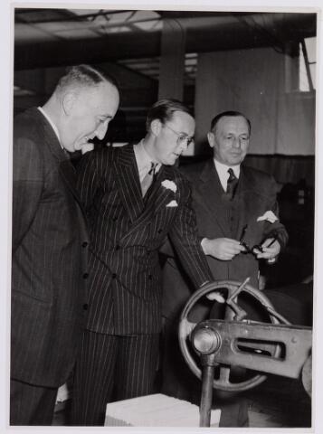 037677 - Textielindustrie. Prins Bernhard kijkt vol belangstelling naar een machine die de afgewerkte stukken op een rol wikkelt