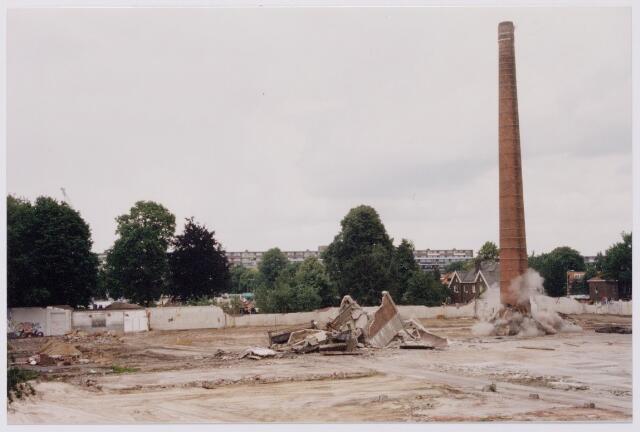 043839 - Het opblazen van de fabrieksschoorsteen op het terrein van de Regenboog aan de Bredaseweg.