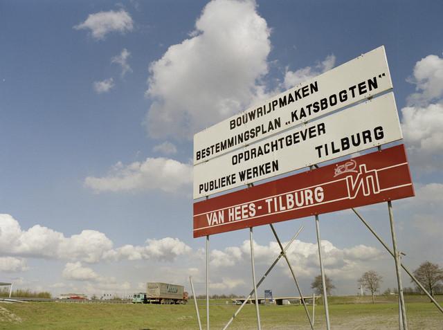 """TLB023000147_001 - Rijksweg A58 met autoverkeer ter hoogte van de afslag Goirle, Tilburg, Turnhout en Efteling  Bord met aankondiging van het bouwrijp maken van bestemmingsplan """"Katsbogten"""" door de firma Van Hees uit Tilburg in opdracht van Publieke Werken Tilburg. Foto genomen in kader """"SPB / BouwRai"""" ter promotie van het """"Samenwerkingsverband Praktijkopleiding Bouw"""" en de tweejaarlijkse bouwmaterialenbeurs in de Amsterdamse RAI."""