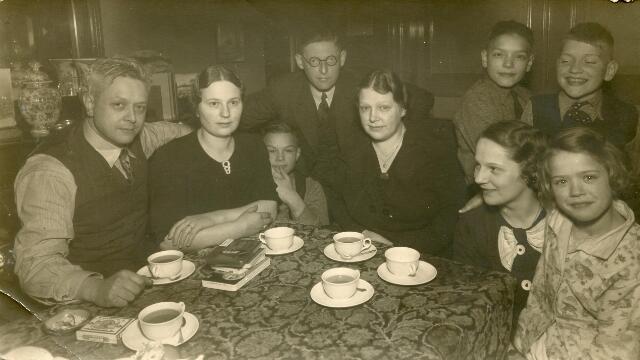 602017 - Interieur van de woonkamer Zomerstraat 37, woning en fotostudio van Piet van der Schoot (1896-1960). Van links naar rechts fotograaf Piet van der Schoot, Fien de Bont-van Eijck, zoon van der Schoot, Frans de Bont, Miet van der Schoot-van Eijck, Joos van Eijck en drie kinderen van der Schoot.