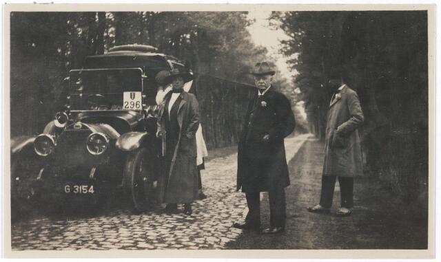 006689 - mevrouw Brouwers-van Waesberghe en enkele heren naast een auto (kenteken G3154) en een herkenningsbord met het wapen van Amsterdam nr.296 op een landweg.