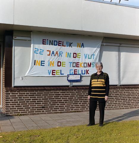 """1237_001_014_008 - De Diensten Centrale een de Havendijk in Tilburg. Een feestelijke bijeenkomst in verband met een pensioen / VUT in oktober 1994. De pensionaris staat bij een spandoek: """"Eindelijk na 22 jaar in de VUT. Ine in de toekomst veel geluk""""."""