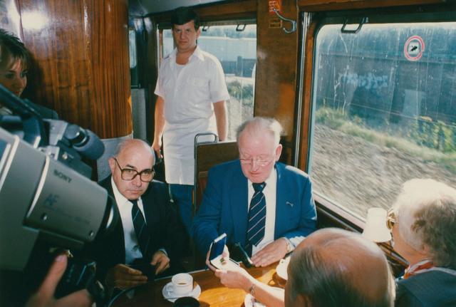 651289 - Tilburg, 125 jaar stad aan het spoor. Manifestatie. Oud-burgemeester (Tilburg) Henk Letchert (rechts) neemt als eerste de herdenkingspenning in ontvangst. De penning was een grote verrassing en werd uitgereikt door medewerkers van Algemene Bank Nederland aan alle gasten in de trein. Het was een geste van de sponsoren van de trein.