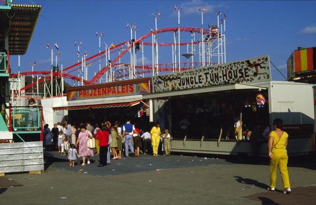 656441 - Tilburg kermis in 1984. Te zien is een achtbaan, prijzenpaleis en Jungle fun house.