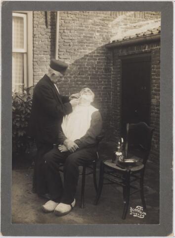 006364 - Volksfiguren: De huis aan huis kapper of barbier. Hier is Woutje LEIJTEN aan het werk, dorpsbarbier in de Hasselt, Van Hogendorpstraat. Met zijn koperen zeepbakje en waterketeltje trok hij van klant naar klant. Zie ook foto 5046.