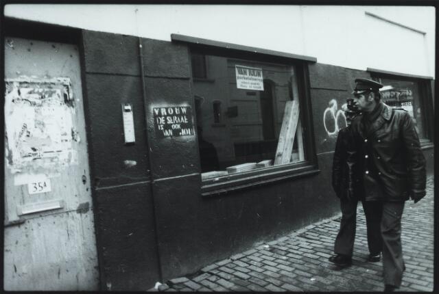 033591 - Parkeerwachten wandelen door de Tuinstraat en passeren pand nummer 35a. Links graffiti en affiches.