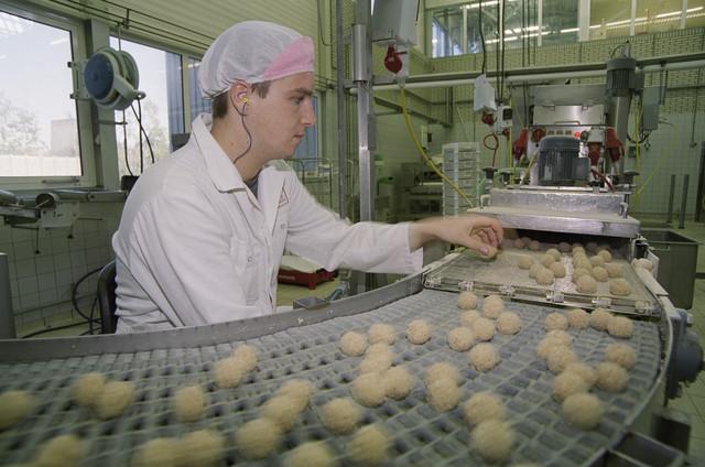 TLB023000904_002 - Werknemer aan de lopende band met bitterballen bij Breti snacks.