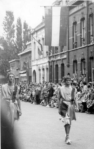 """064758 - Op 18 september 1955 trok de eerste Heilig Hartstoet in nieuwe vorm door de straten van Tilburg. De stoet werd ontworpen door Luc van Hoek en gefinancierd met bijdragen van particulieren, uit het bedrijfsleven en door de zogenaamde """"zakjeactie"""", die ruim 6000 gulden opbracht. De leiding van de stoet was in handen van regisseur Van Erp. Rooms Leven sprak na afloop over """"een stad vol gelukkige mensen"""". De stoet trok """"als een weldaad door de stad, als een groot en indrukwekkend feest, een godsdienstige plechtigheid, die als het ware heeft laten zien dat Gods liefde waarlijk een boeiende en ontroerende roman is""""."""