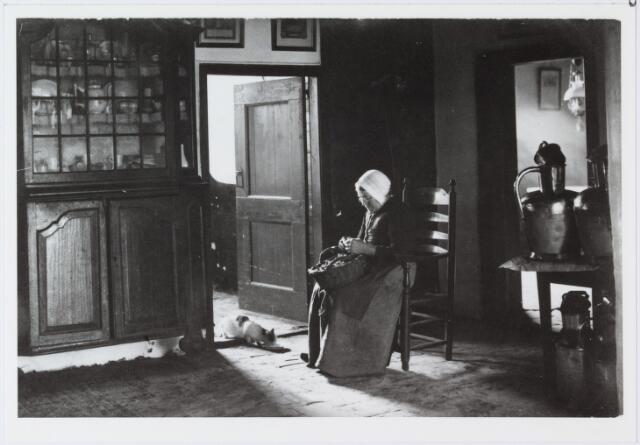 006944 - Mien van Gompel-Verbunt geboren te Helvoirt 12 september 1852 overleden te Udenhout 19 mei 1923. interieur met poes; vrouw gezeten op stoel in deuropening; schilt aardappels; Enschotsebaan café De Rustende Jager.