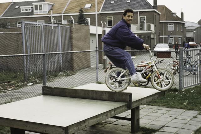 """TLB023000416_010 - Jongen met crossfiets op een ping-pongtafel in een """"stads-speeltuin. Foto gemaakt in het kader van (on-)veilige speelsituaties en t.b.v. een kinderspel infocentrum"""