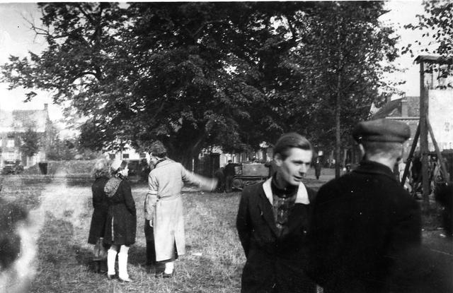 830048 - WO2: WOII; Tweede Wereldoorlog. Bevrijding. Op de foto o.a.  'Ron Naaijkens.' in gesprek. Op de achtergrond is een tank zichtbaar
