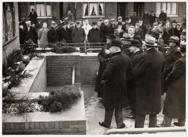 104049 - Onthulling van de zitbank op het plein voor de R.K. Kerk van de H. Antonius van Padua aan de Hoefstraat te Tilburg aangeboden door de familie A.J. Claessen (rechts). Uitlegging van de voorstellingen voorkomende op de bank door de ontwerper architect J. van der Valk aan genodigden bij de onthulling.