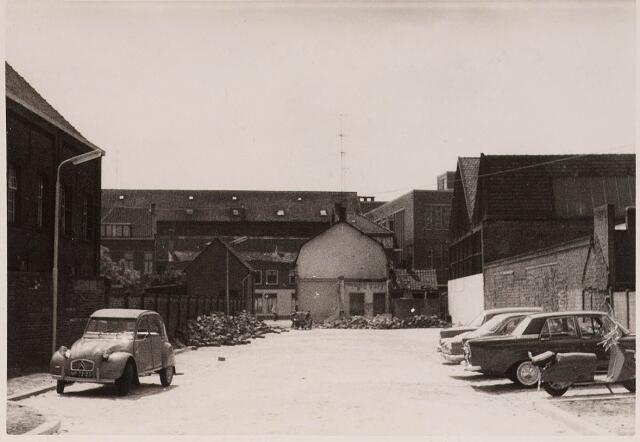 028421 - Parkeerterrein met fabriekspanden en woonhuizen voor de afbraak.