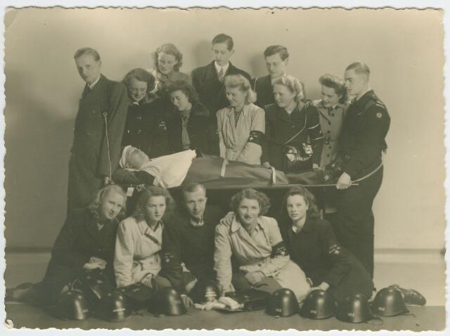 064601 - Kinderen van middenstanders uit de Willem II-straat vormden tijdens de Tweede Wereldoorlog de EHBO-afdeling van blok 102. Op de eerste rij v.l.n.r. Annie van de Velden, Lien Vermeer (slagerij), Leo Ceulen (kapper), Corry Vermeer en Roosje v.d. Beld. Het slachtoffer in het midden is Tijn de Wekker (boekhandelaar). Staande op de volgende rij v.l.n.r. Ton v.d. Brekel, Carla v.d. Brekel, Nellie Aarts (sigarenmagazijn), Selma Valkenberg (van de wapenhandel), May van de Velden, Sita Valkenberg en Jan Aarts. De drie personen op de laatste rij zijn v.l.n.r. Netty v.d. Brekel, Harry Wassing (reisbureau, andere bronnen noemen Theo of Karel Wassing) en Jos v.d. Brekel. De groep kreeg de EHBO-beginselen bijgebracht door mevrouw v.d. Beld.