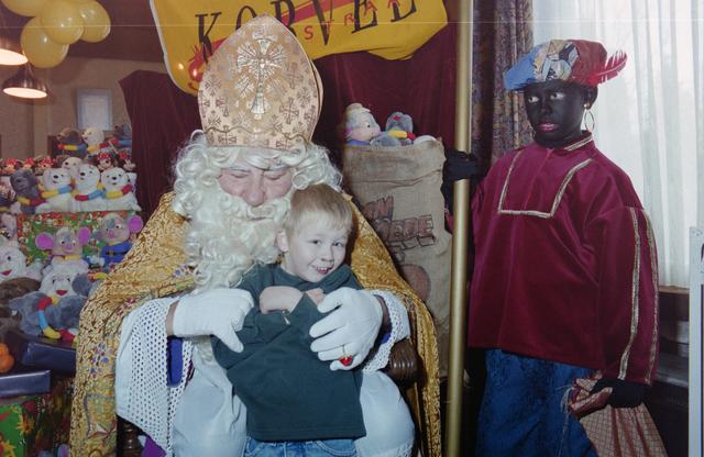 1237_001_003_018 - Feest. Korvel Winkelstraat. Sint Nicolaasviering. Een kind poseert met Sinterklaas en Zwarte Piet tijdens een Sinterklaasfeest georganiseerd door winkeliersvereniging Korvel Vooruit op 27 november 1999. Op de achtergrond staan de cadeautjes.