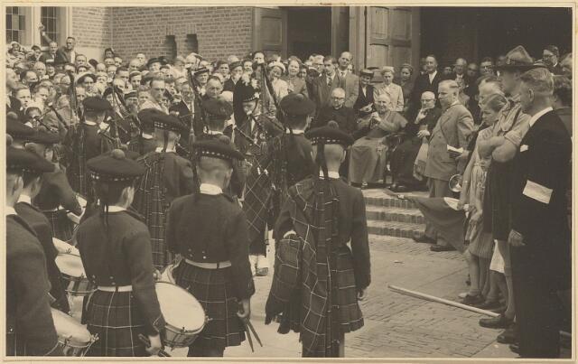 604022 - Parochie Gasthuisring; Optreden op het kerkplein van drumband de 'Schotjes' ter gelegenheid van de inwijding van de nieuwe kerk O.L. Vrouw van Altijddurende Bijstand. Zittend: pastoor Jansen (van deze parochie) en Mgr. Mutsaerts (rechts naast hem).