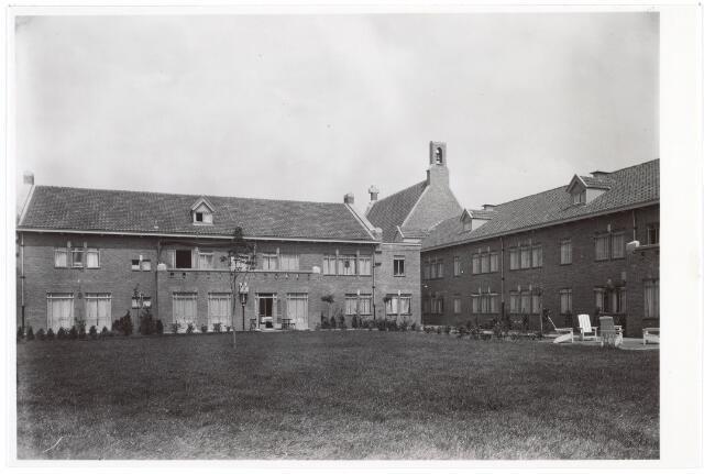 016784 - Mariëngaarde. Tuin van pension Mariëngaarde met zicht op de kapel en Noordvleugel. Dit was het domein van de zusters (gutjesnonnen), waar ook de keuken en eetzaal was gevestigd. Rechts het terras bij de conversatiezaal.