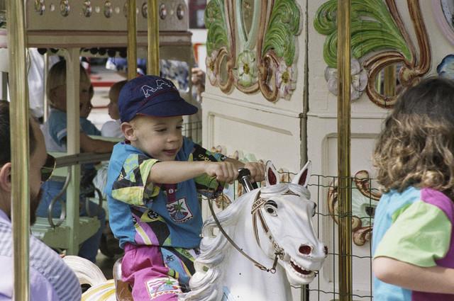TLB023000196_001 - Kinderen in de draaimolen op de Tilburgse Kermis.  De Tilburgse Kermis is de grootste kermis in de Benelux. Er staan jaarlijks tussen de 230 en 240 attracties uit binnen- en buitenland, in een 4,5 kilometer lang lint door het centrum van de stad. De kermis trekt jaarlijks meer dan een miljoen bezoekers en is daarmee een van de best bezochte evenementen van Nederland.