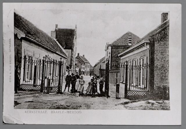 065518 - Vanaf het Kerkplein een gezicht in de Kerkstraat omstreeks 1905. Het grote gebouw links is de pastorie van Baarle-Hertog, bewoond door de pastoor L. Ph. Ghijsels (1886-1920); deze pastorie was gebouwd in 1775 en tijdens het verblijf van genoemde pastoor grotendeels verbouwd. Achter het hek links mej van Hecke, tussen het open hek links H. van der Kuijlen en daarnaast H. Verhoeven. De drie kleine kinderen rechts zijn Lisa, Jan en Jos Slockers; de woning rechts wordt bewoond door de gemeentesecretaris Schurmans