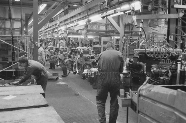 TLB023002470_005 - Deze monteurs zijn in een aandrijflijn bezig met motorblokken te monteren