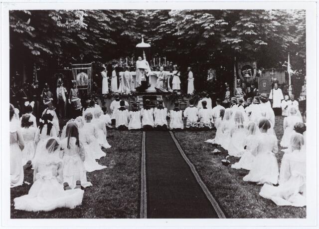 011628 - Sacramentsprocessie naar Petrus Donders op 3 juni 1956. Openluchtlof bij rustaltaar in kruiswegparkje. pastoor Meulemans van de parochie Heikant geeft zegen met het Allerheiligste.