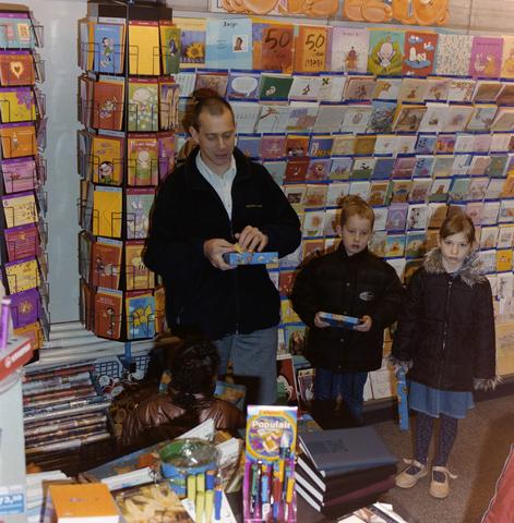 1237_001_005_005 - De prijsuitreiking van een kleurwedstrijd in een kantoorboekhandel aan de Korvelseweg in december 2001. De winkelier feliciteert de kinderen en overhandigd de prijzen in zijn winkel. De wedstrijd was een initiatief van winkeliersvereniging Korvel Vooruit.