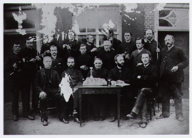 057058 - Handboogschutterij Muraena te Moergestel, opgericht in 1886. Foto genomen voor café Kerkzicht. Achter de tafel burgemeester Willem van Heeswijk.
