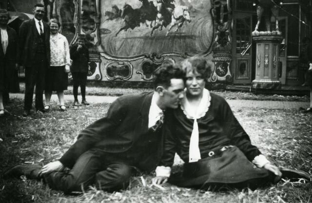066029 - Een stelletje zit lekker in het gras op het Stuivesantplein.  Dit plein heeft ook ooit als kermisterrein gediend.