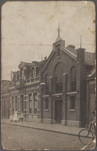 011200 - De kerk van de gereformeerden aan de Lange Nieuwstraat. Het gebouw is ontworpen door S. Wierda uit Amsterdam, architect en hoofdopzichter bij de aanleg van de Staatsspoorwegen. In 1874 is het is gebruik genomen als 'Evangelisatie-locaal'. De formatie van een gereformeerde kerk in Tilburg kreeg pas haar beslag op 8 november 1894. Het gebouw deed dienst als kerk tot november 1923. Toen werd  door de gereformeerde gemeente van Tilburg een kerk aan het Molenbochtplein in gebruik genomen. Op verzoek van de Raad van de Gereformeerde Kerk te Tilburg werden kerkgebouw, vergaderlokaal en pastorie aan de Lange Nieuwstraat in 1923 verkocht. De kerk kwam in handen van gymnastiekvereniging Olympia, die het verbouwde tot trainingszaal, kleedlokalen en vergaderruimte. Links van de kerk de pastorie o.a. bewoond door H.J. Binnema, die in 1887 vanuit Oostende naar Tilburg kwam. In Oostende was hij werkzaam als bijbellezer-colporteur. Te Tilburg werd hij in 1892 aangesteld als dominee. Hij overleed er op 12 november 1909. Zijn opvolger en bewoner van de pastorie was dominee J. de Vries, geboren in Burum. Op de foto voor de pastorie zijn dienstmeid Pietje den Baas (1883-1918)  met zijn drie kinderen Barbara (1908), Gerritdina (1910) en Jacob (1911) de Vries.