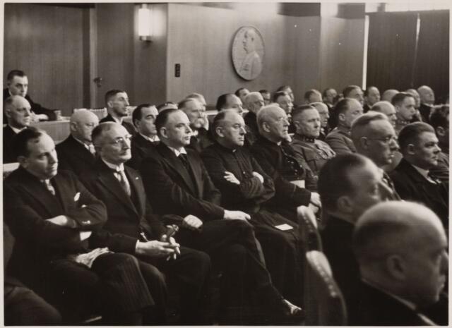 103386 - Installatie van burgemeester mr. J.C.A.M. van de Mortel. Foto van genodigden tijdens de openbare Raadszitting. voorgrond links de heer Fortgens, 5e zelfde rij: deken F.J. Sanders parochie Noordhoek.