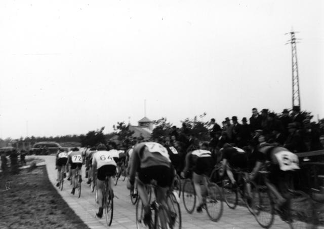 105608 - Ronde van de Warande. Wielerwedstrijd. Sport. Wielrennen. Het peloton op de rug gezien. Fietsen op een tegelpad.