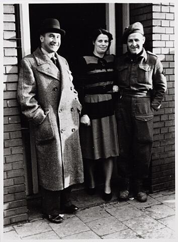 012869 - Tweede Wereldoorlog. Inkwartiering. Een bij een particulier ingekwartierde militair poseert aan de voordeur met zijn gastheer en -vrouw