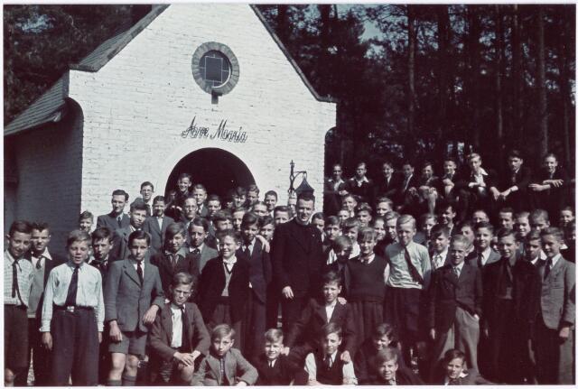 051231 - Basisonderwijs. r.k. lagere school. St. Jozefschool. Leerlingen van de St. Jozefschool uit de wijk Broekhoeven ll in Tilburg met kapelaan Tychon bij de Mariakapel aan de weg Tilburg-Loon op Zand.