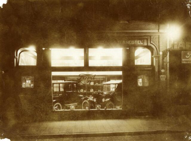 """200104 - Etalage van garagebedrijf Knegtel aan de Heuvel. Het bedrijf werd officiëel opgericht op 24 mei 1913 als Automobielbedrijf Knegtel & Wagemakers. De vennootschap met L.J. Wagemakers werd ontbonden op 1 december 1915, waarna Theo A.M. Knegtel, """"mecaniciën, koopman en garagehouder"""" alleen verder ging. Een maand later, op 25 januari 1916, trouwde hij te Veghel met Henriëtte J.A.C. van den Heuvel. Het bedrijf verkocht vanaf 1913 Opel automobielen en rijwielen van het merk Oswond. Vanaf 1916 verkocht de firma ook Excelsior Motoren en vanaf 1921 is Knegtel Forddealer voor Tilburg en omgeving."""