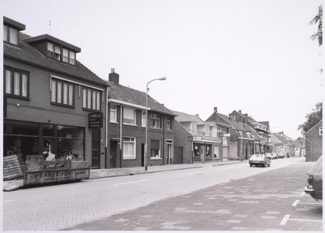 024979 - Laarstraat omstreeks 1982, met links de winkel in bouwmaterialen en ijzerwaren van Mels en daartegenover het kerkhof