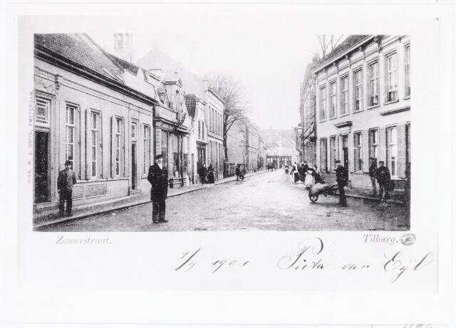 040083 - Zomerstraat. Geheel rechts nog een raam dat hoort bij het pand van de familie Boelaars. Links daarvan pand M457, vanaf 1910 Zomerstraat 40. Rond 1900 woonde in dit pand Johanna Rosalia Knegtel, geboren te Tilburg op 16 mei 1841, met haar kinderen. Zij was weduwe van Jan Baptist van Enschot, burgemeester van Goirle. In 1908 verhuisde de weduwe Van Enschot naar de Lange Nieuwstraat. Daarna is dit pand gesloopt voor de bouw van een nieuw huis voor notaris Van Eijl. Links het gedeelte van de Zomerstraat tussen de Schoolstraat en de Nieuwlandstraat. Deze panden waren in 1900 bekend als de panden M731 t/m M742. In 1900 woonden hier v.l.n.r. notaris Van Eijl, boekbinder H.L. Geerling, koperslager C. Luijben en H.J. Briels, huisschilder en spiegelfabrikant.