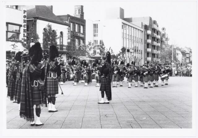 043383 - Op 27 oktober 1984 werden allerlei festiviteiten en herdenkingen gehouden b.g.v. 'Tilburg 40 jaar bevrijd'. Hier trekt een groep militaire wagens over de Heuvel van de organisatie 'Keep them rolling'. Hier taptoe door een pipersband.