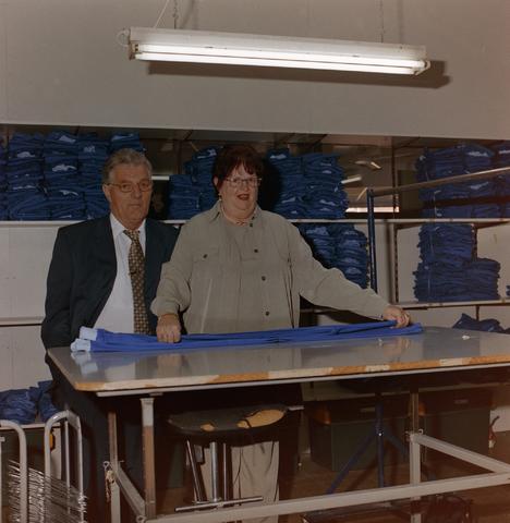 1237_001_021_003 - Een medewerkster van de Tilburgse Diensten Centrale aan de Havendijk vouwt blauwe kledingstukken in november 2000. Iemand van de directie kijkt mee.