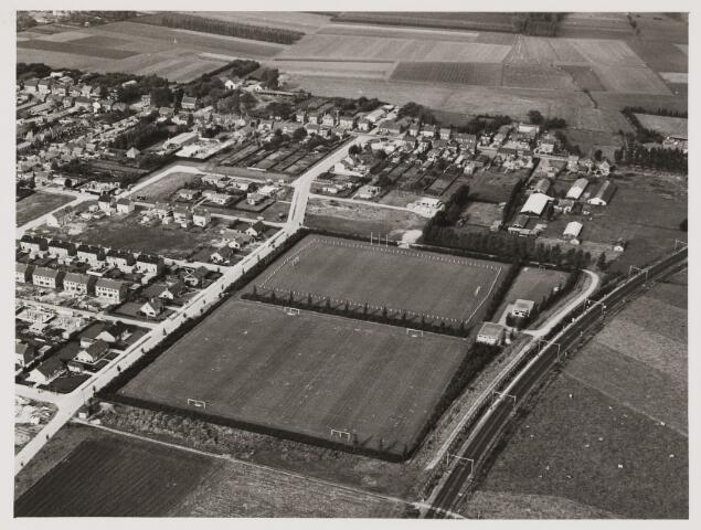 080409 - Luchtfoto's van Udenhout. Rechts het spoor tussen Tilburg en 's-Hertogenbosch. Daarnaast in het midden het sportpark met de sportvelden. Links nieuwbouwwijk de Zeshoeven II. Rechts kippenkooien van IJseldijk, hier werd later de Wilgenlaan aangelegd.