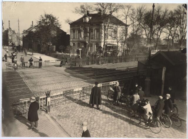 027299 - Spoorwegovergang. Ter hoogte van thans NS Plein No.'s 17, 16, enz, tot 10. Midden foto: No. 10. Overweg Koestraat. De villa is in 1935 afgebroken.Spoorwegovergang Heuvel/Besterd. De straat achter het spoor heette toen nog Koestraat. Nu is de Besterdring de verbinding tussen Heuvel en Besterd.  Rechts villa Eleonora, gesloopt in 1935. De laatste bewoner was dokter Van Baar. Eerder woonden er de familie Mutsaerts-Diepen en in de negentiende eeuw M.J.J.H. Lommen, majoor-commandant van de dienstdoende schutterij. Ter plaatse heet het nu  N.S.plein.