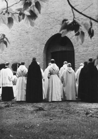 105213 - Kloosters. Sint Paulusabdij. Monniken (op de rug gezien) voor de ingang van de kerk. Kerkwijding van de nieuwe kloosterkerk van de Sint Paulus Abdij in Oosterhout, gebouwd tussen 1953 en 1956 onder architectuur van J. Sluymer uit Enschede.