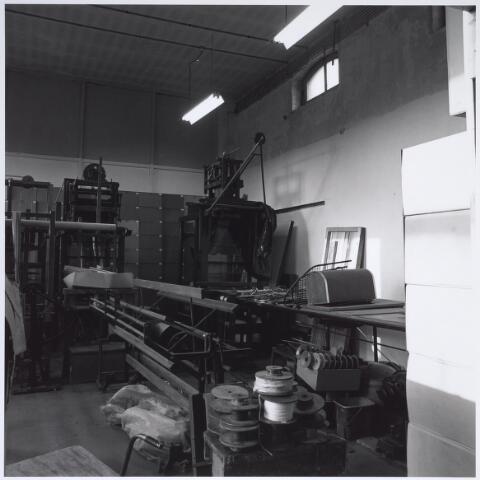 025300 - Interieur van het voormalige St. Rochus Gasthuis aan de Lange Nieuwstraat kort voor de sloop. De onderdelen van textielmachines in deze opslagruimte herinnert aan de periode dat het gebouw enige tijd onderdak bood aan het textielmuseum