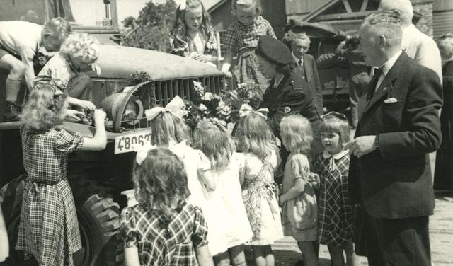 1696070 - Kinderen helpen leden van het Rode Kruis met het versieren van de truck. Waarschijnlijk is dit rondom de steun vanuit het Rode Kruis België aan waarschijnlijk Rijen of Hulten in verband met de oorlogsverwoestingen omstreeks 1945. Foto uit de collectie van het Nederlandse Rode Kruis afdeling Tilburg. Bevrijding. WOII.