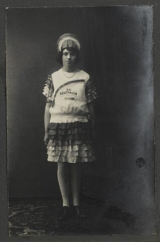 071905 - Meisje in een jurk in regenboogkleuren maakt reclame voor ververij en chemische wasserij De Regenboog uit Tilburg.