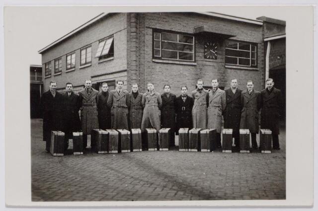 044363 - WOII; WO2; Textielindustrie. In het najaar van 1942 werd personeel van textielfabriek Enneking aan de Goirkestraat slachtoffer van de Arbeitseinsatz. De foto werd genomen op het fabrieksterrein voor het vertrek. De timmerman van het bedrijf, Jan Spijkers, had de houten koffers getimmerd voor de arbeiders. Enneking zorgde voor levensmiddelen, zeep enz. Zevende van links Jaoneke Kuijpers, in de fabriek bekend als een vrolijke man en gangmaker. Links van Kuijpers Toon Jansen. Hij kwam op 22 juni 1943 om het leven bij een bombardement op Krefeld.