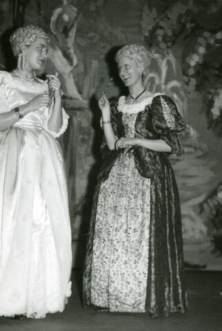 """092046 - Op de Diës-viering van de St. PAULUS-HBS op 17 maart 1961 werd 's avonds het toneelstuk """"Leonce en Lena"""" van G. Büchner opgevoerd.  Links:  Bea Hendriks als Prinses Lena, van het rijk van Pipi,  en Marie-José Elissen als gouvernante van prinses Lena."""
